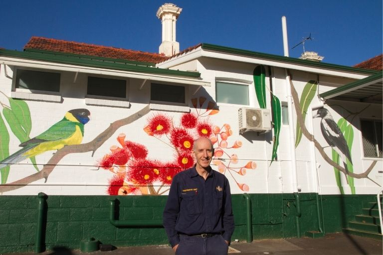 A man stands in front of a large mural of native flora and fauna on a building wall.