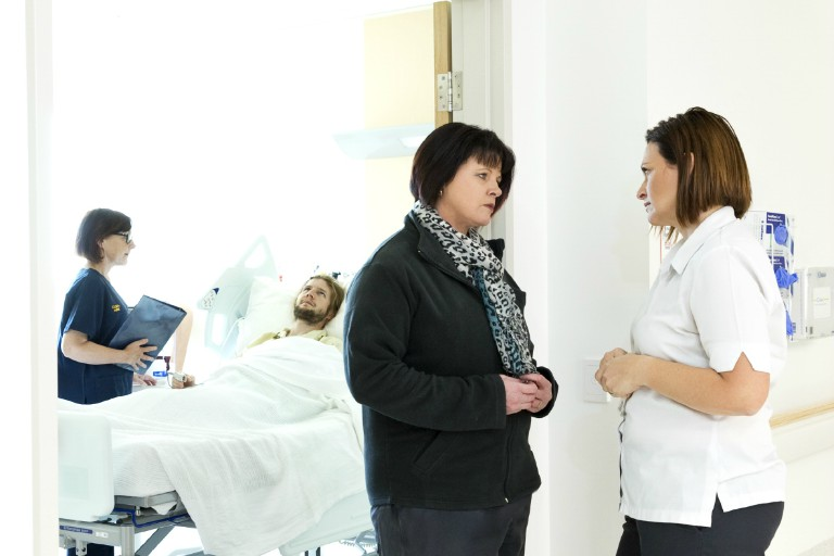 A nurse standing by the bedside of a male patient, with two women standing talking in a nearby doorway
