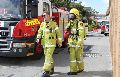 Two fire fighters standing beside a fire engine