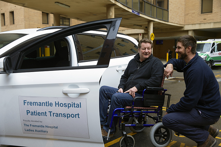 Two men in conversation beside a car. One man is sitting in a wheelchair. A sign on the car door read 'Fremantle Hospital Patient Transport'.