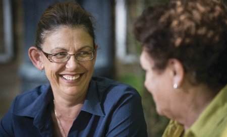 Woman smiling and talking to another woman