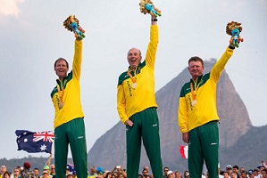 Three men in Australian Paralympic uniforms standing on the winners podium