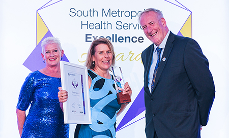 Two women and a man stand in front of a banner that reads South Metropolitan Health Service Awards. One woman holds a certificate and an award trophy.