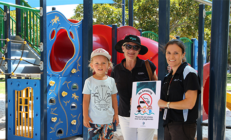 A young boy stands with two woman in front of colourful playground equipment. One woman holds a certificate that reads Please do not smoke near our playgrounds.