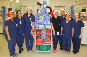 Recovery Theatre clinical staff standing around a Christmas tree made from blue surgical gloves