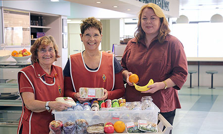 Three women stand behind a trolley that holds healthy fruit and drink options.