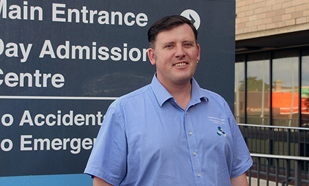 John Harris stands in front of a sign that reads 'Main entrance' and Day Admission Centre'.