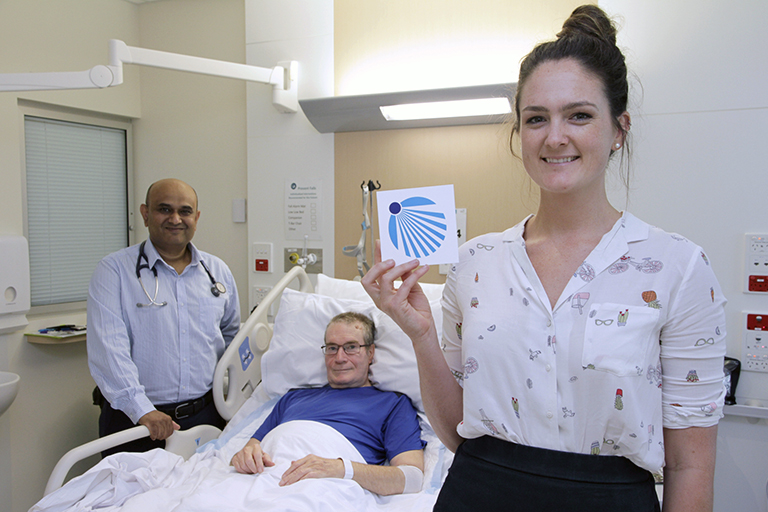 A young woman stands beside a man laying in a hospital bed. She holds a small card that features a blue logo. Another man stands on the other side of the hospital bed.
